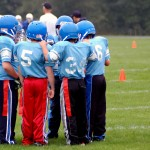 Boys huddle during a game of flag football.