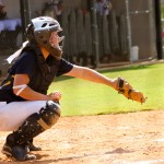 Young girl playing catcher in a softball game.